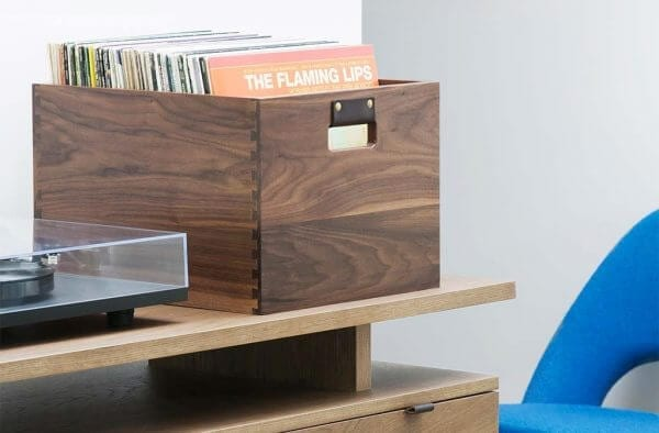Dovetail Vinyl Record Storage flip bin constructed with premium North American hardwoods and a dark natural walnut wood finish. It is sitting next to a Modern Record Player.