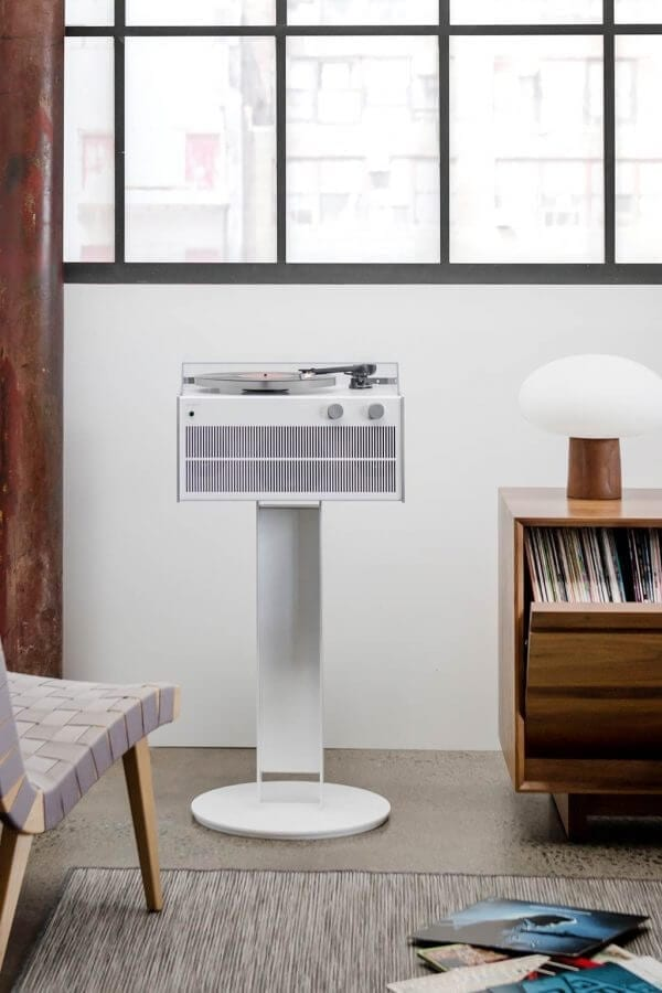 Modern Record Player with bright white exterior on sturdy record player stand to create high-fidelity sound with a custom hand-built amplifier in a living room setting. It stands next to a premium swivel style LP storage cabinet.