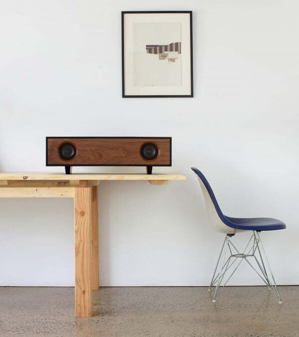 Tabletop Hifi speaker with a dark natural walnut finish. Crafted with North American hardwoods. It sits at 28.75 inches wide and 9.5 inches tall and weighs 30 lbs. It is sitting on tabletop in a living rooming setting.
