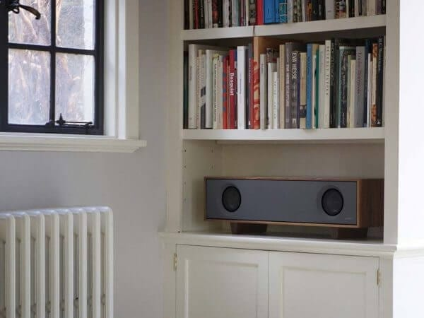 Tabletop Hifi speaker with a dark natural walnut finish. Crafted with North American hardwoods. It sits at 28.75 inches wide and 9.5 inches tall and weighs 30 lbs. It is displayed on a living space bookshelf.